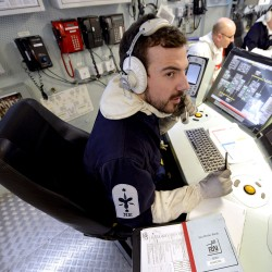 A Royal Navy Marine Engineering Electrical Technician is pictured at a console in the Ship Control Centre (SCC) of Type 45 destroyer HMS Diamond.