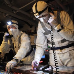 Engineering Officers onboard HMS Illustrious coordinate the ships firefighting teams during a hectic exercise aimed at pushing the ship to its limits.